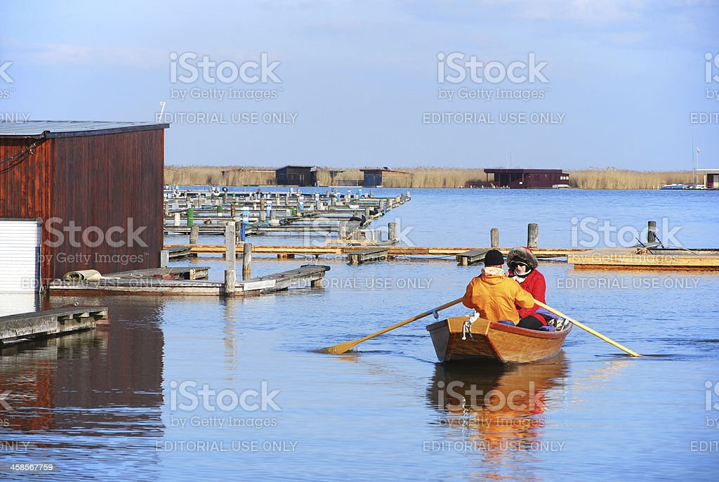 Couple in a rowing boat at lake neusiedlersee winter royalty-free stock photo