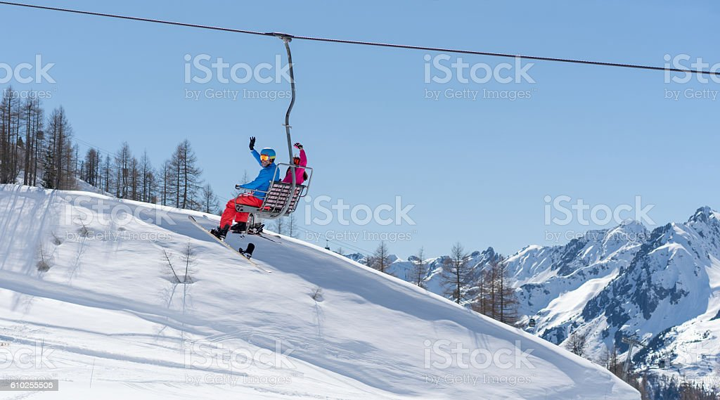 Couple in a ski lift chair stock photo