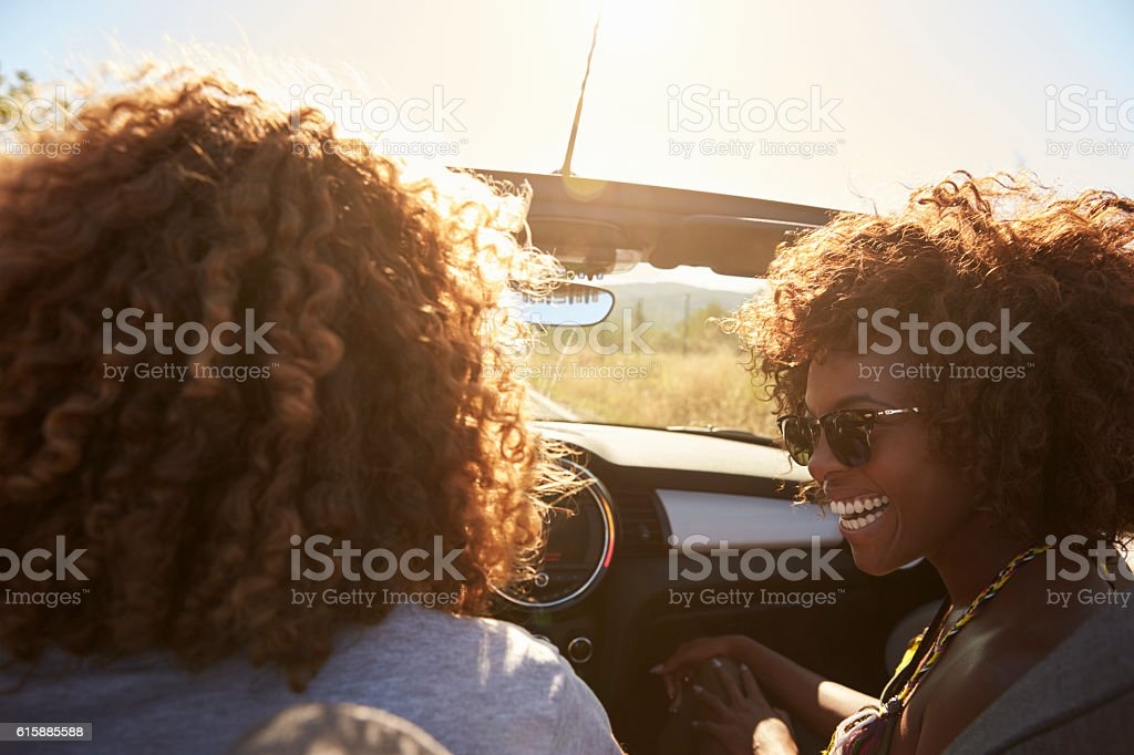 Couple in an open top car, rear passenger point of stock photo