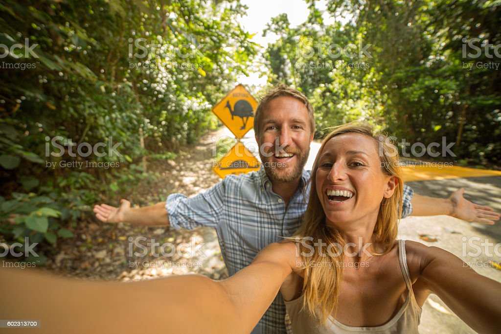 Couple in Australia take selfie with humorous cassowary road sign stock photo