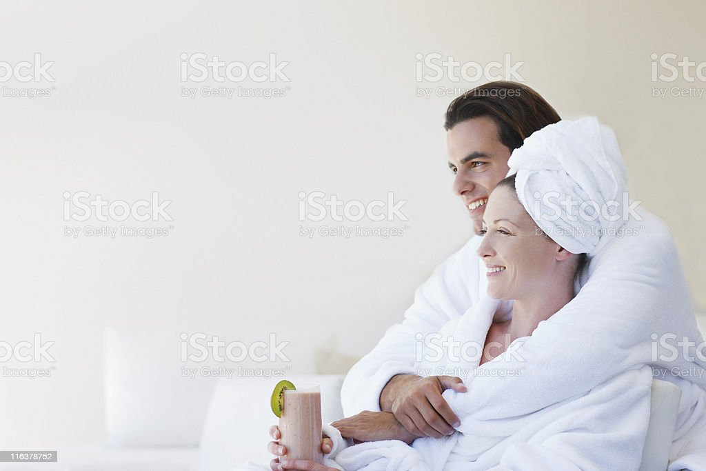 Couple in bathrobes hugging royalty-free stock photo
