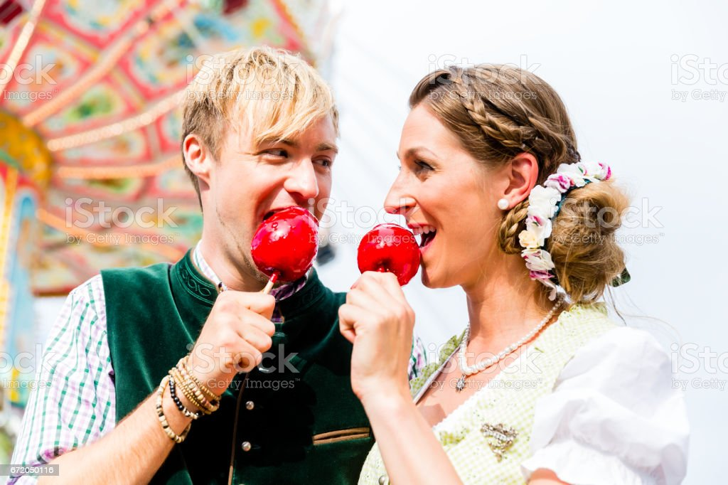 Couple in Bavarian clothes eating candy apples stock photo