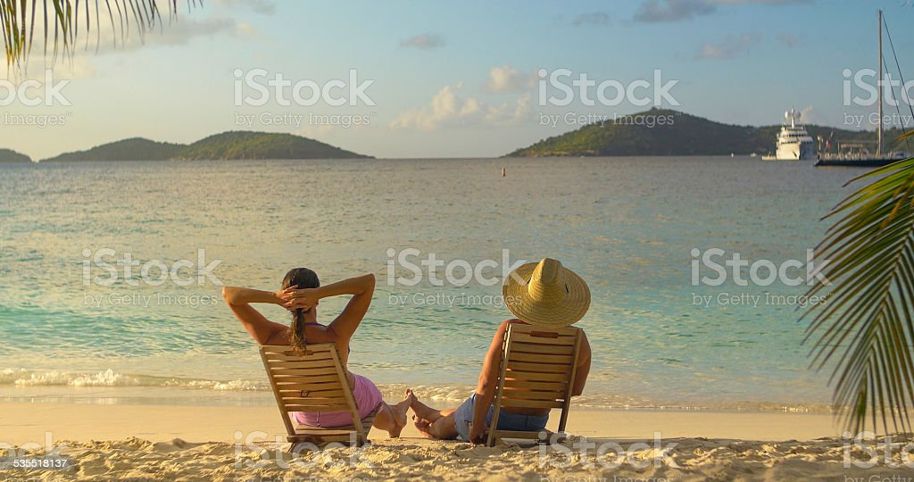 couple in beach chairs, playing footsie and watching sunset stock photo