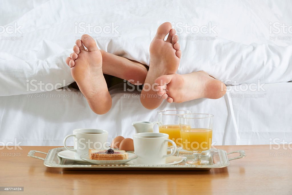 Couple in bed and breakfast tray stock photo