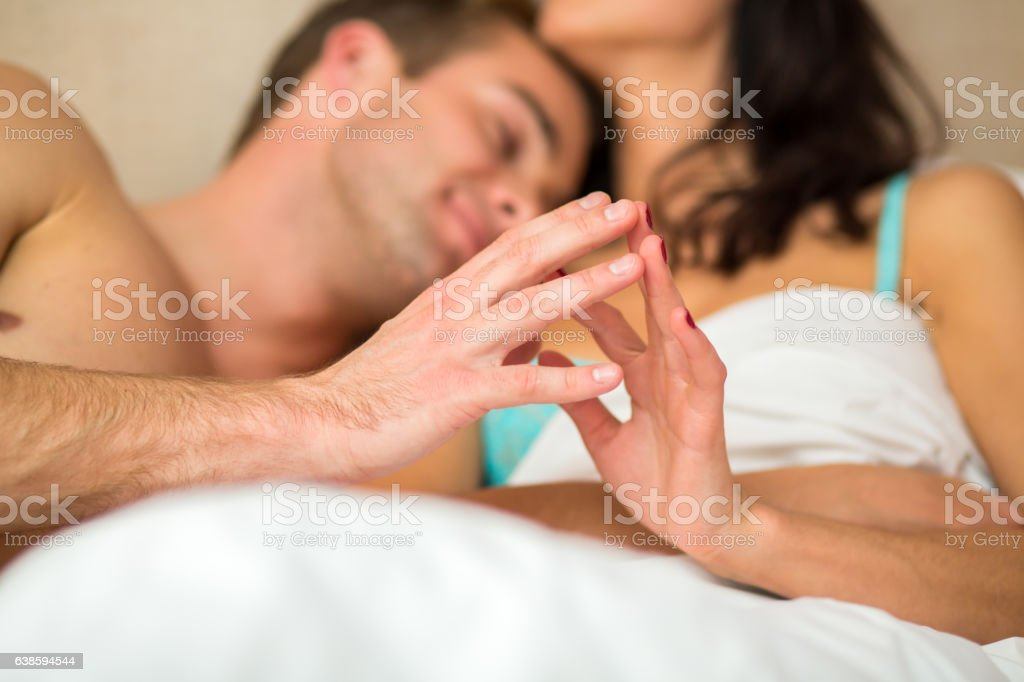 Couple in bed touching hands. stock photo