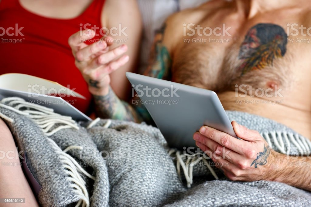 Couple in bed with digital tablet and book. stock photo