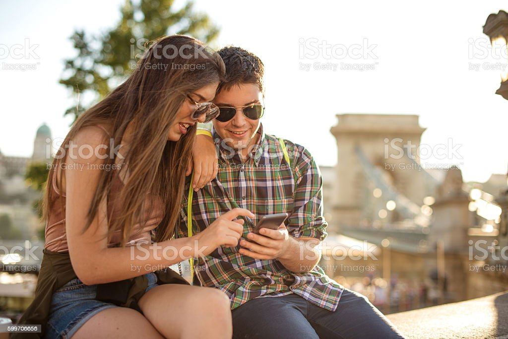 Couple in Budapest using app on smartphone for landmarks stock photo