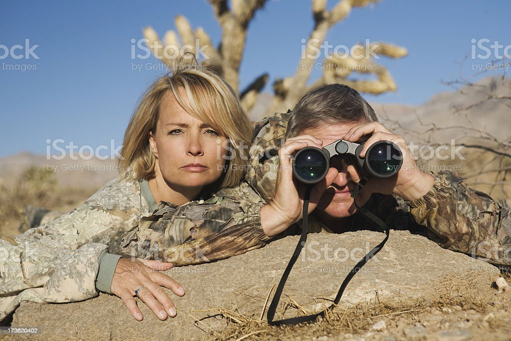 Couple in camouflage gear watching the enemy with binoculars stock photo