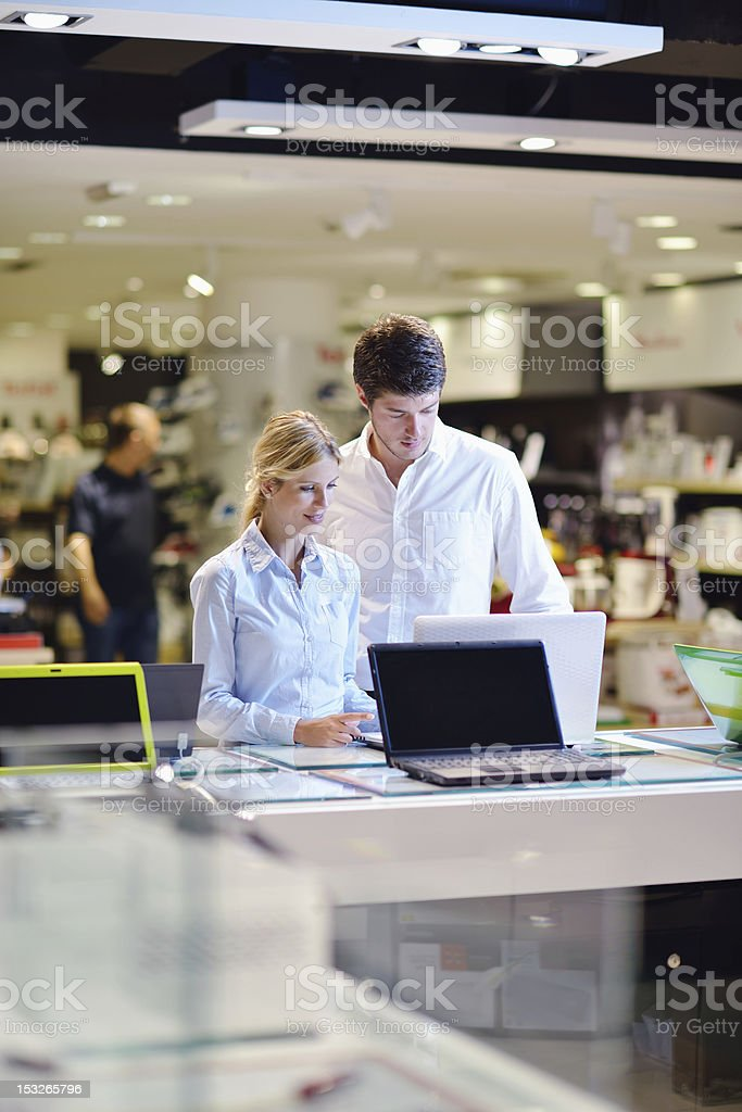 couple in consumer electronics store buying laptop stock photo