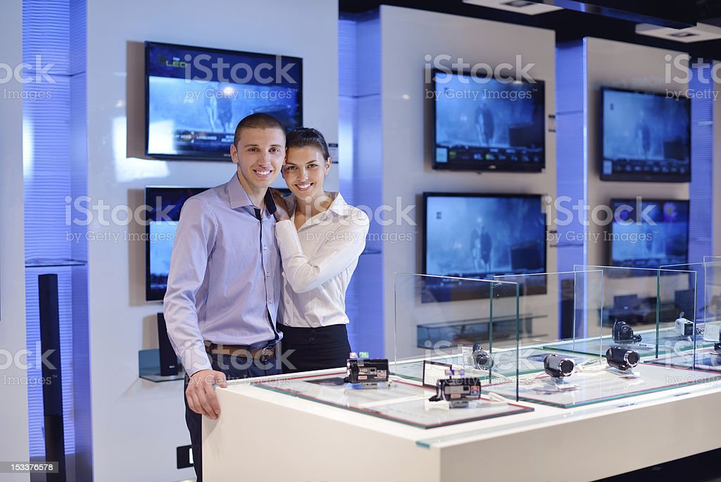 couple in consumer electronics store buying photo camera royalty-free stock photo