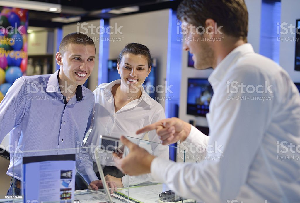 couple in consumer electronics store buying photo camera stock photo