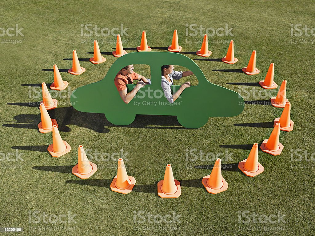 Couple in cutout car surrounded by traffic cones stock photo