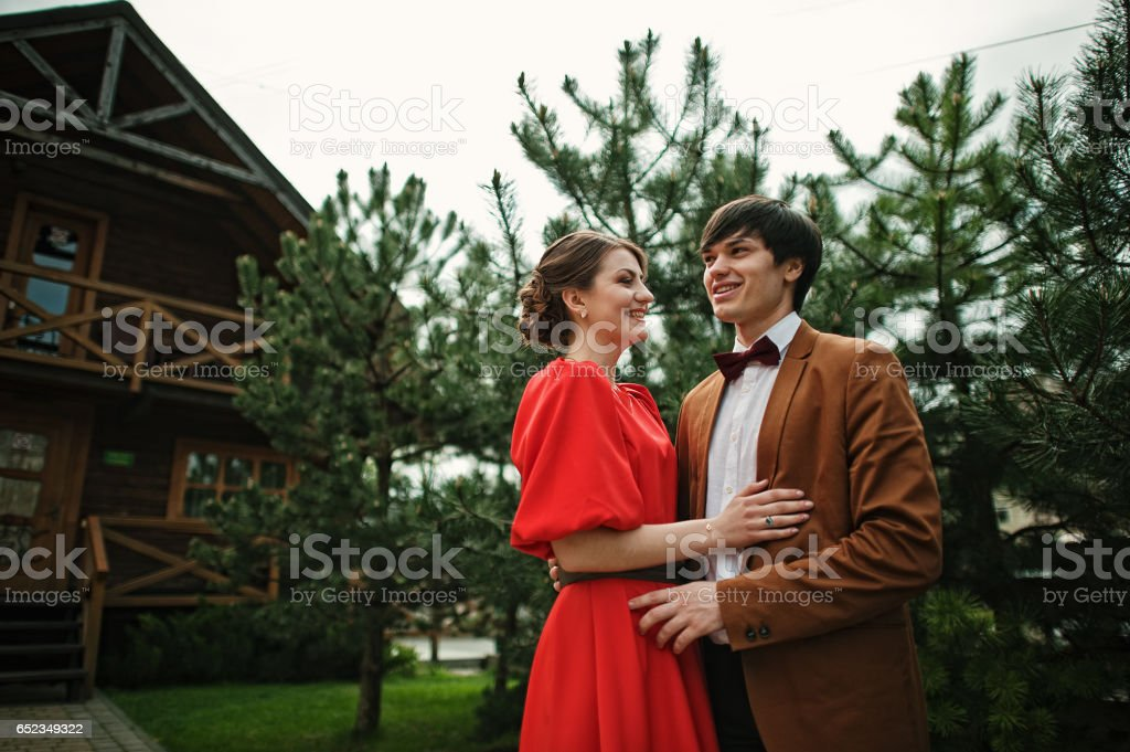 Couple in embrace background conifer trees. Stylish man at velvet jacket and girl in red dress in love together stock photo