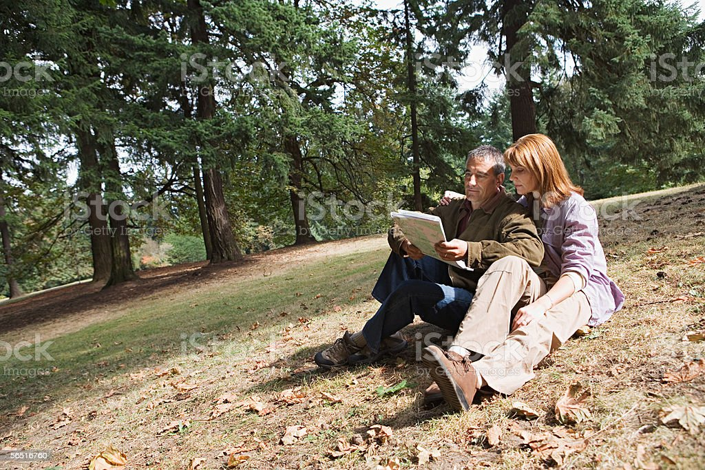 Couple in forest looking at map royalty-free stock photo