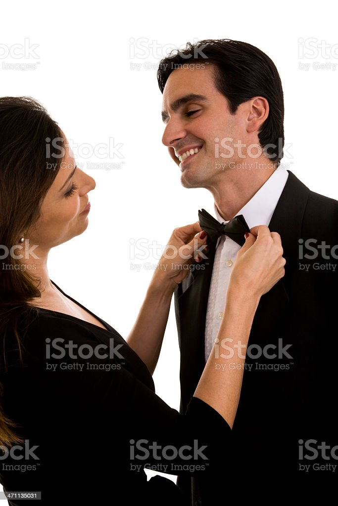 Couple in formal attire, female is fixing man's bow tie stock photo