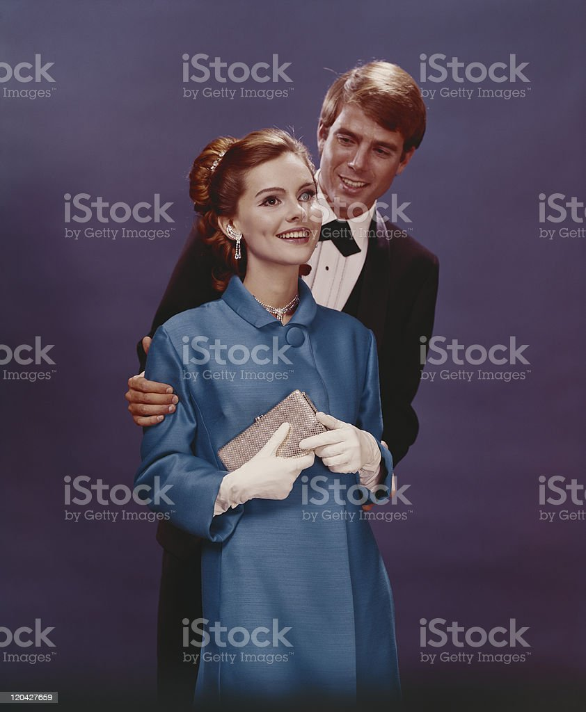 Couple in formal clothing standing against blue background, smiling stock photo