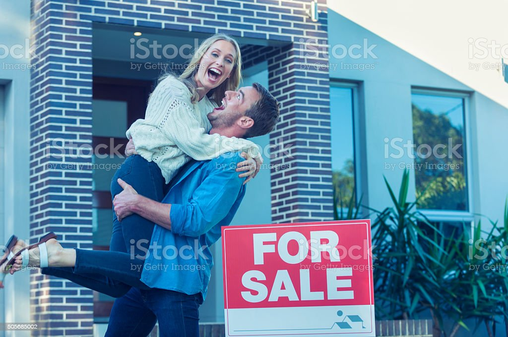 Couple in front of a new home. stock photo