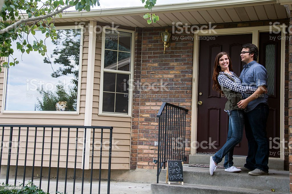 couple in front of doorstep with first house sign stock photo