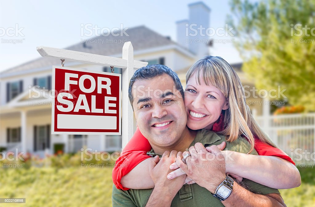 Couple in Front of For Sale Sign and House stock photo
