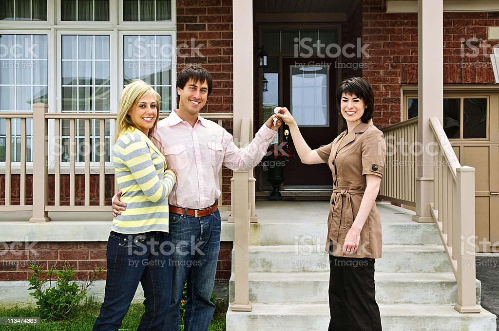Couple in front of house and real estate agent with keys stock photo