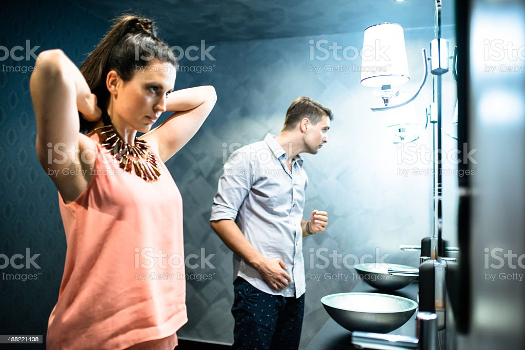 couple in front of mirror before the night out stock photo
