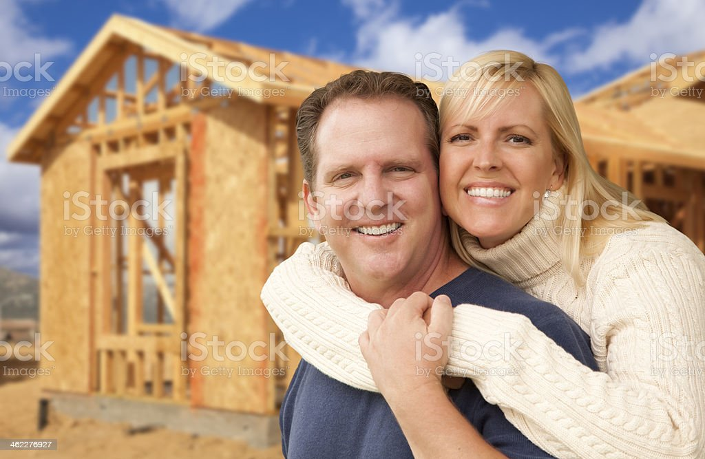Couple in Front of New Home Construction Framing Site stock photo