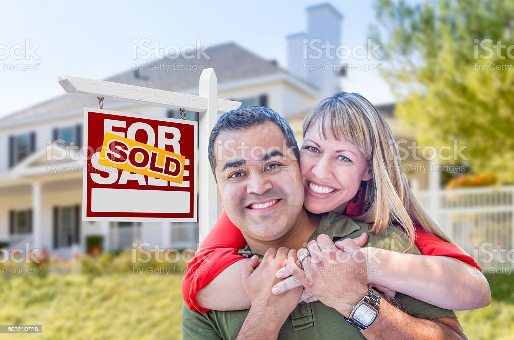 Couple in Front of Sold Real Estate Sign and House stock photo