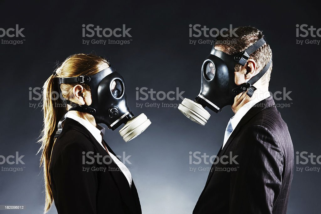 Couple in gas masks face off confronting each other stock photo