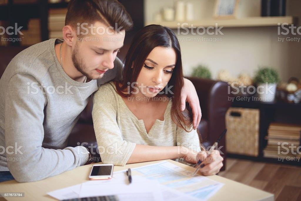 couple in home interior fill out a tax return stock photo