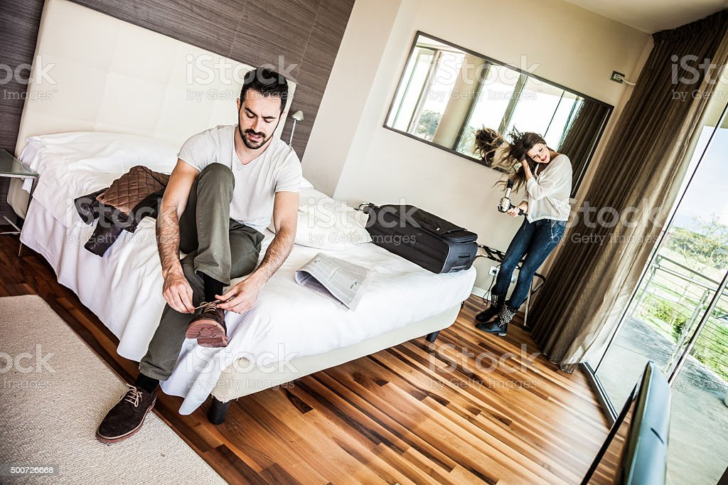 Couple in hotel room getting dressed stock photo