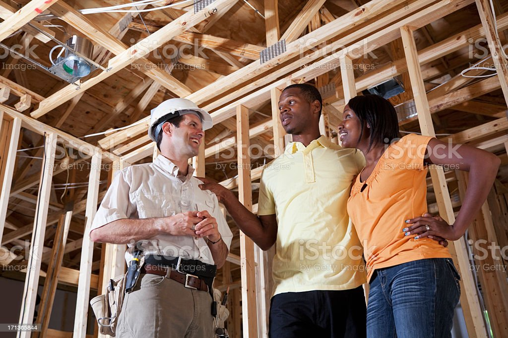 Couple in house under construction with builder royalty-free stock photo