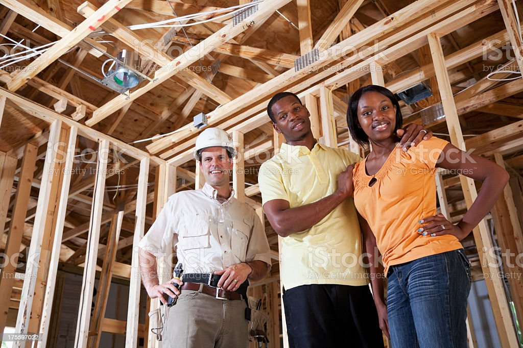Couple in house under construction with builder stock photo