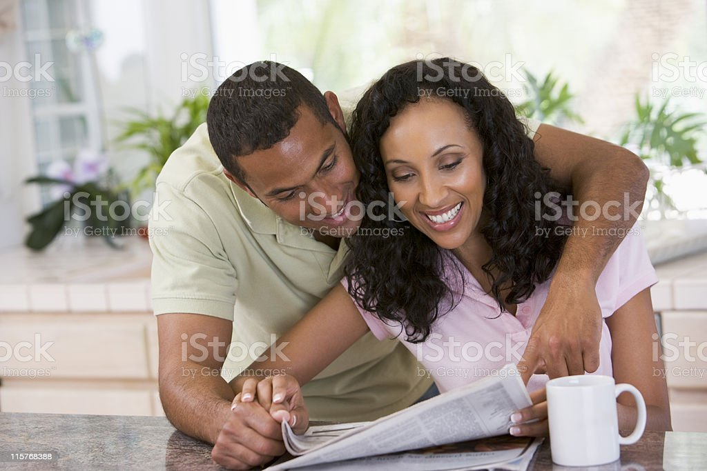 Couple in kitchen reading newspaper with coffee smiling stock photo