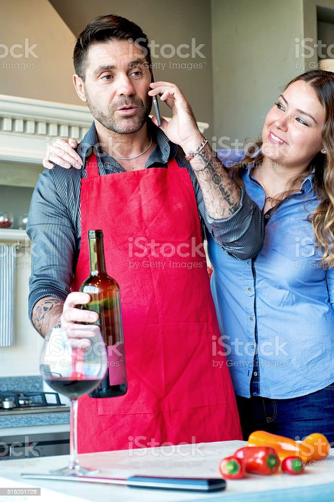 Couple in Kitchen with Red Wine stock photo