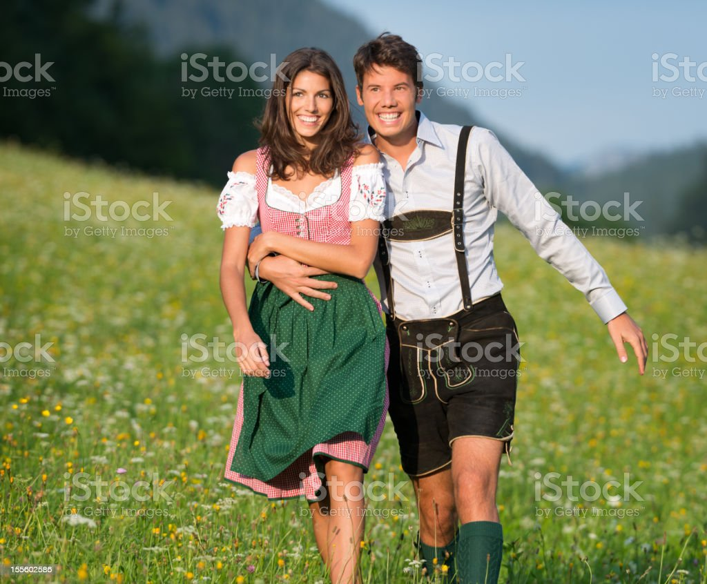 Couple in Lederhose and Dirndl walking through the Meadows (XXXL) stock photo