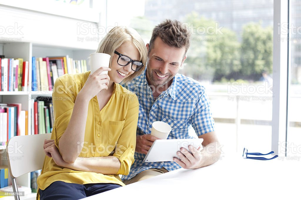 Couple in library working with digital tablet stock photo