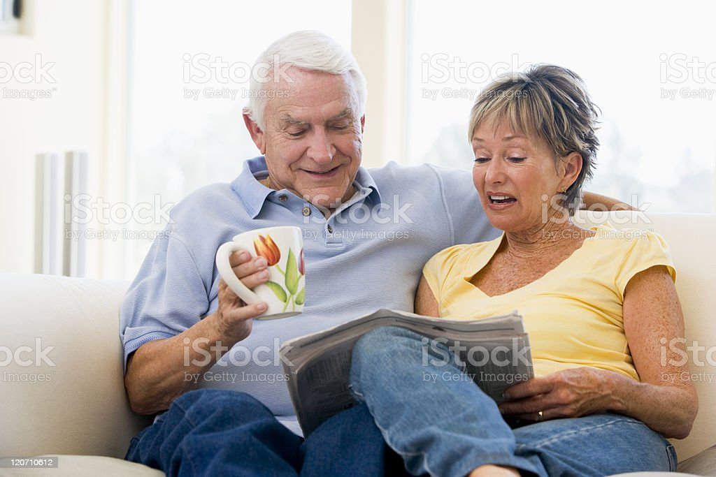 Couple in living room reading newspaper with coffee smiling royalty-free stock photo
