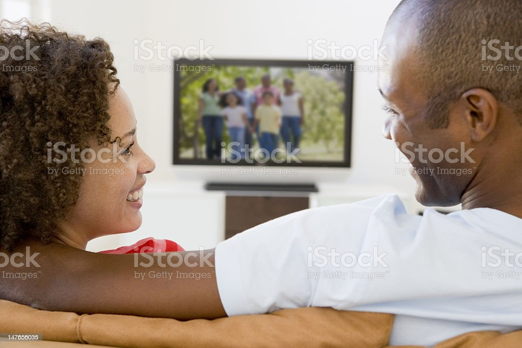 Couple in living room watching television smiling royalty-free stock photo