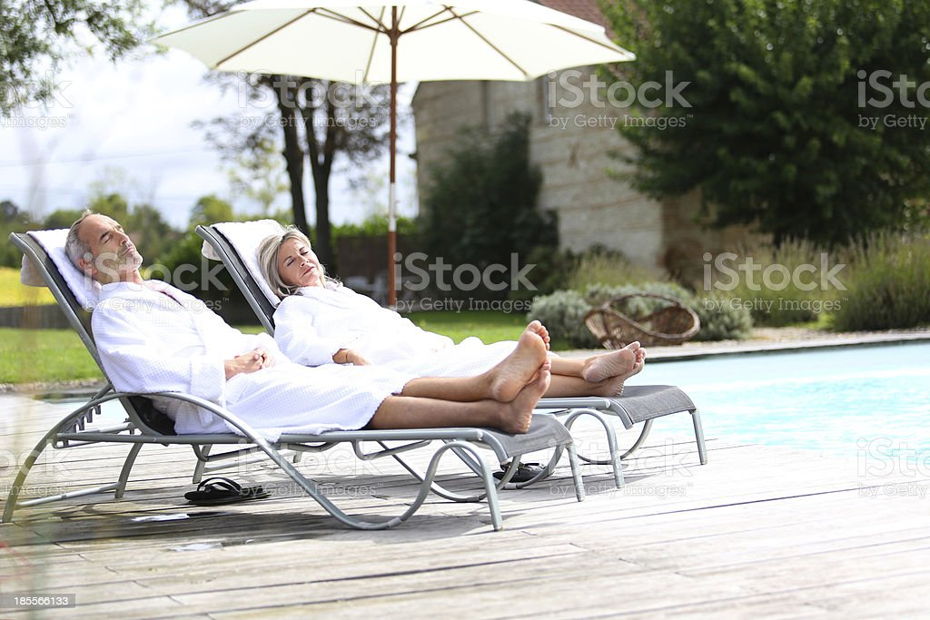 Couple in long chairs napping under parasol stock photo