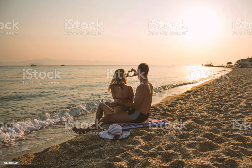 Couple in love at sea sunset stock photo
