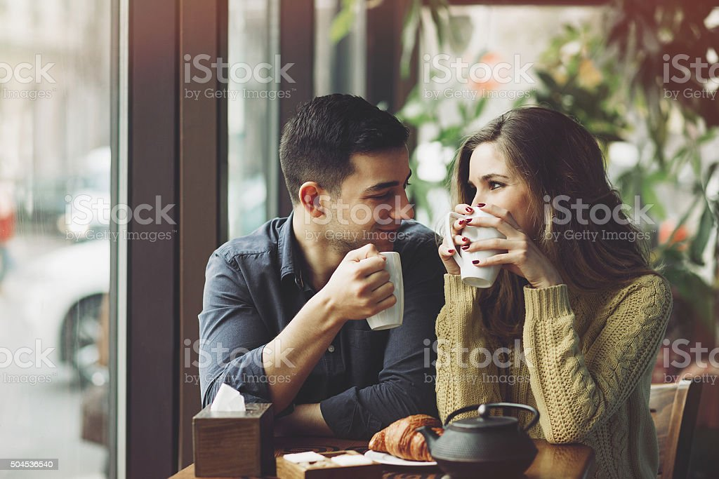 Couple in love drinking coffee and have fun in coffee shop. Love...