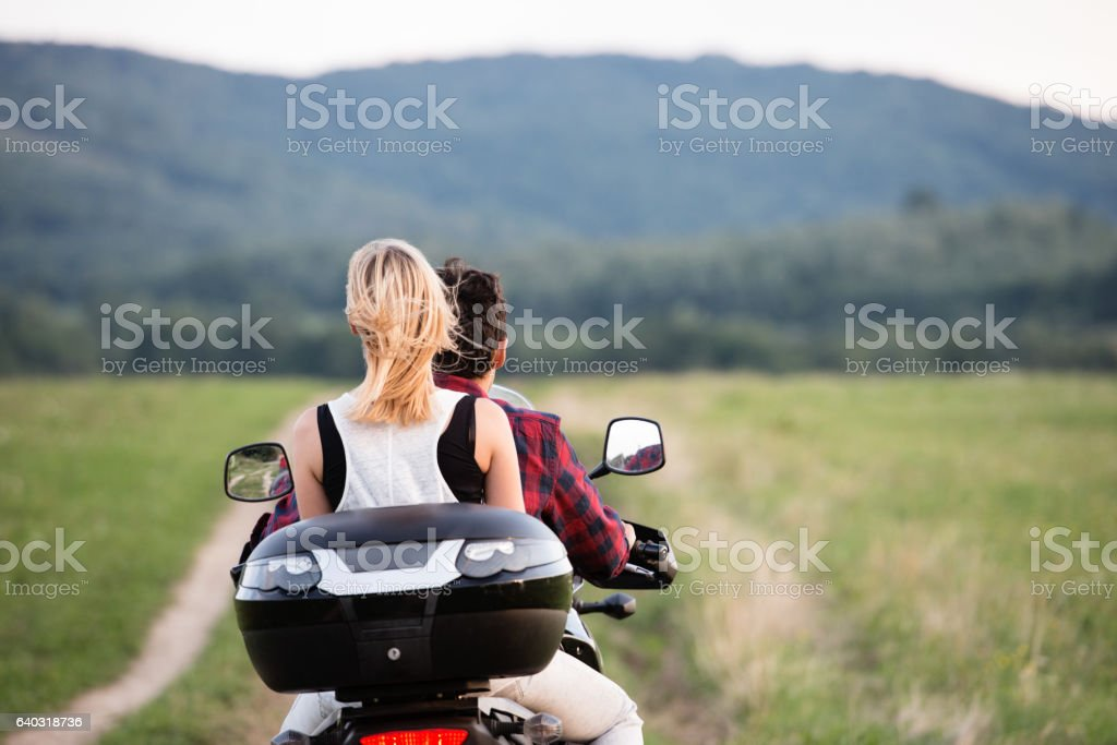 Couple in love enjoying a motorbike ride in countryside. stock photo