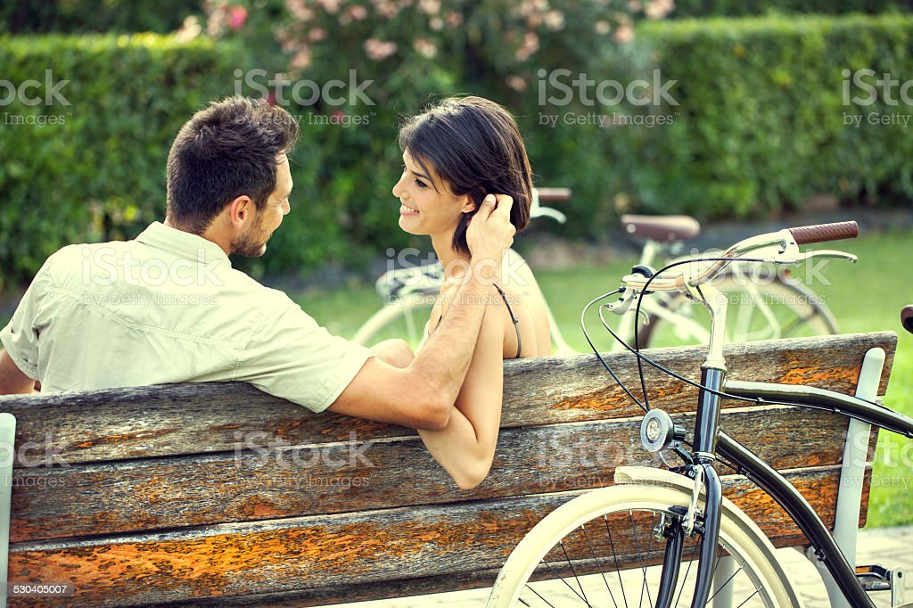 Couple in love fondling herself on a bench with bikes stock photo