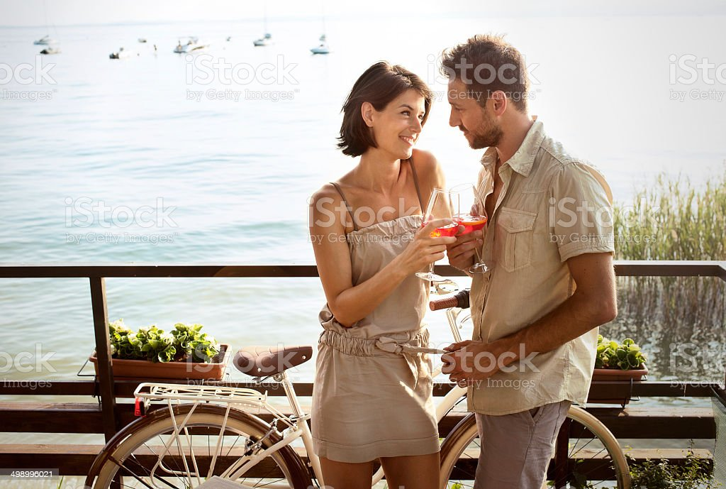 couple in love having spritz time with lake view stock photo