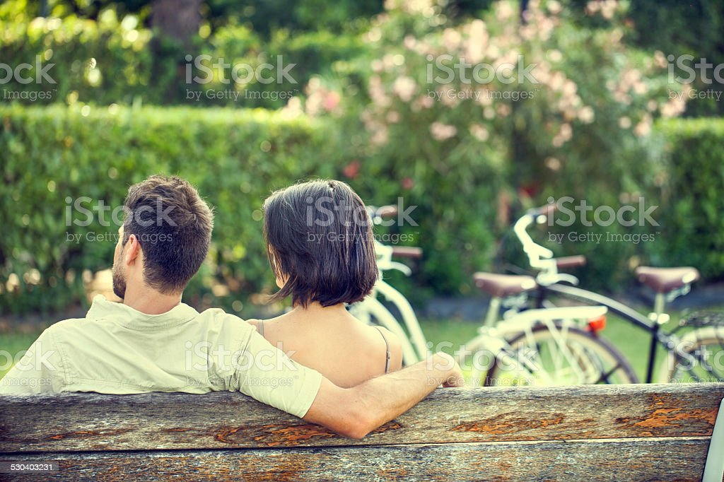 Couple in love hugging each on a bench with bikes stock photo