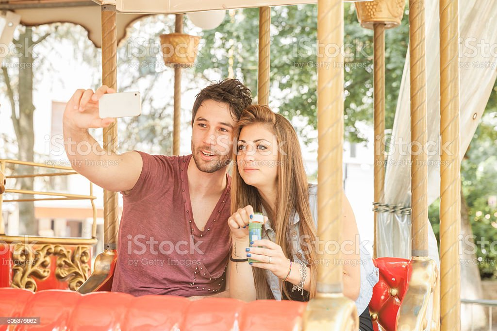 Couple in love making selfie on Merry-Go-Round stock photo