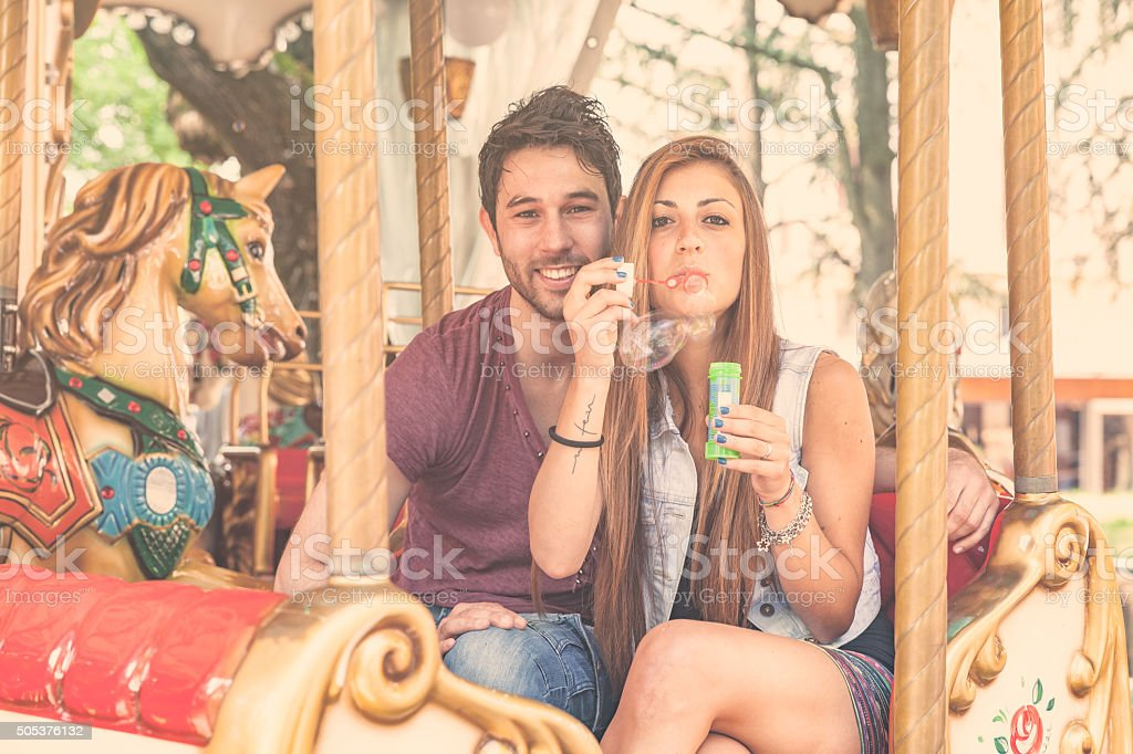 Couple in love playing with soap sud on a carousel stock photo