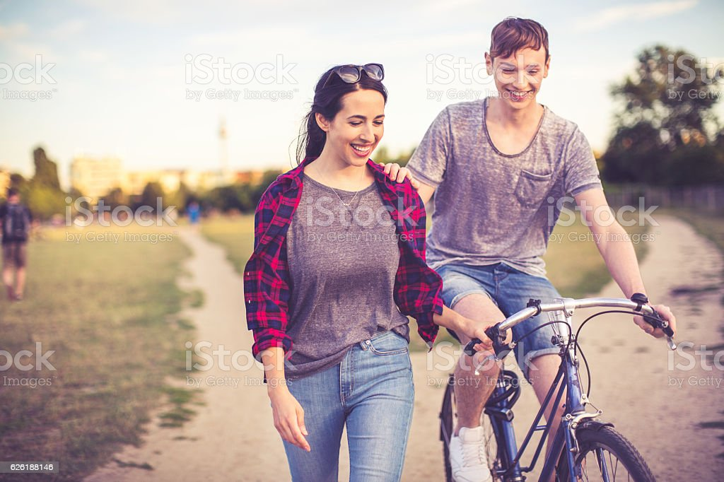 Couple in love riding through a berlin public park stock photo