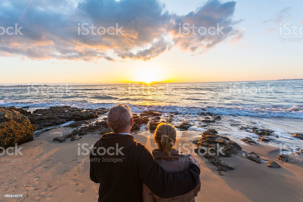 Couple in love watching a sunset on the beach stock photo