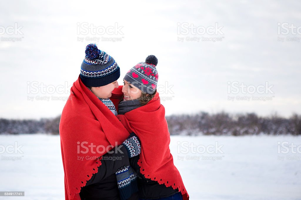 Couple in love with oranges in the winter park stock photo